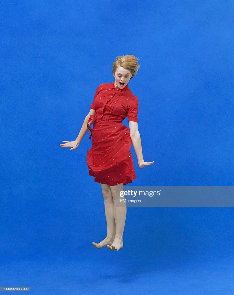 Young woman levitating with  surprise look on face : Stock Photo
