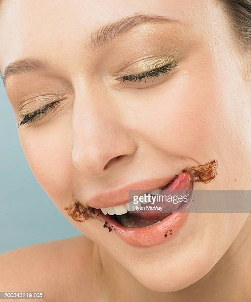 Young woman licking chocolate frosting off face, eyes closed, close-up