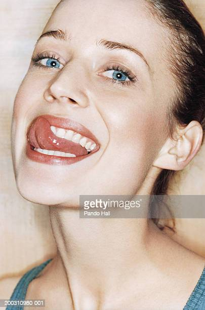 Young woman licking lips, portrait, close-up
