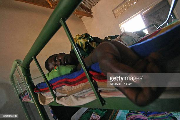 A young woman lies in a bed after recently giving birth at a centre for formerly abducted children 22 February 2007 in Pader town about 250 kms north...
