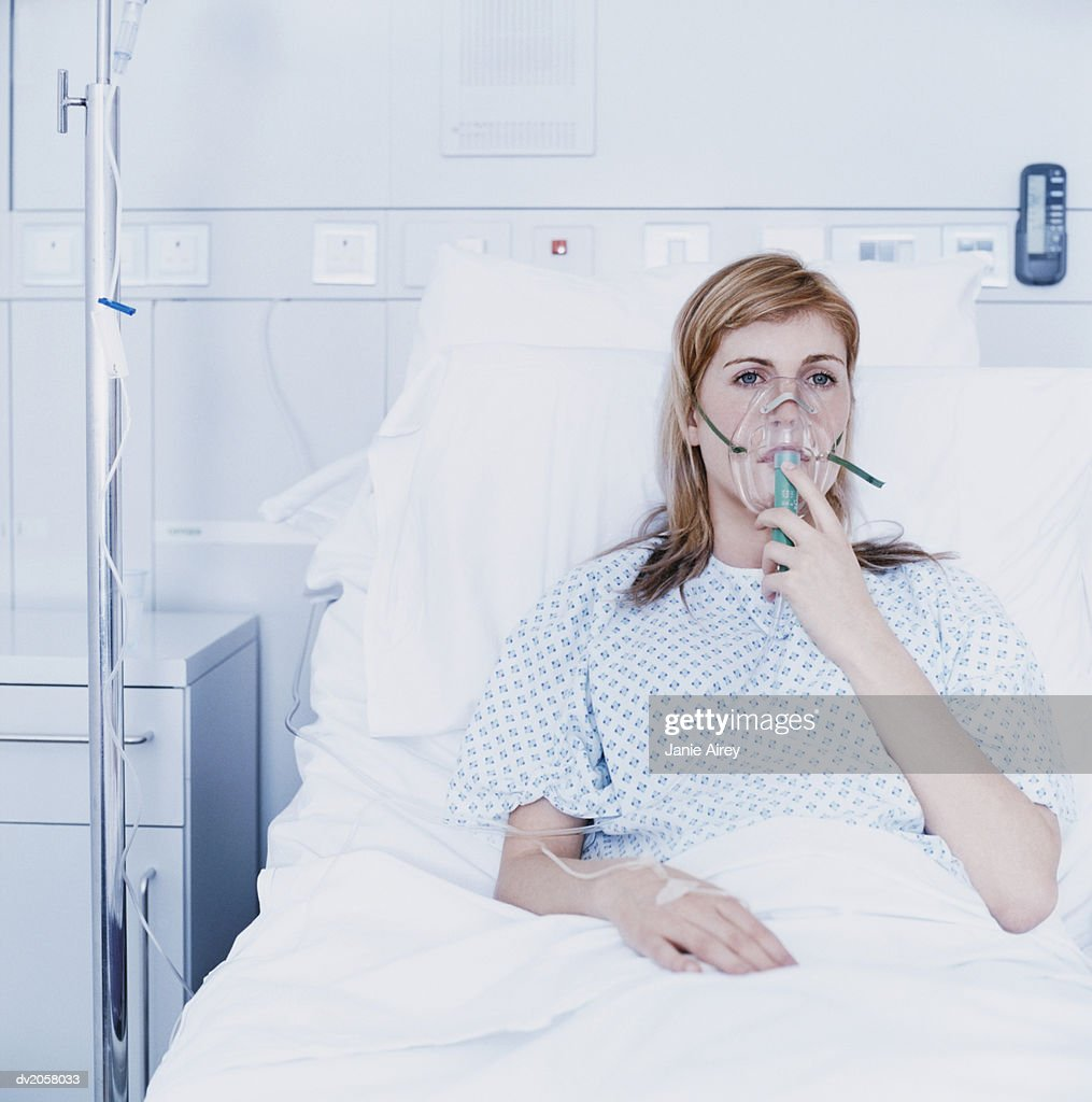 Young Woman Lies in a Hospital Bed on an Intravenous Drip and Breathing Through a Ventilator : Stock Photo