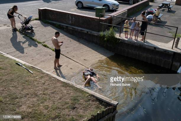 A young woman lies in shallow water after slipping on a boating ramp in Beccles Quay on 13th August 2020 in Beccles Suffolk England