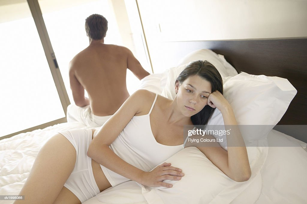 Young Woman Lies on a Bed in Her Underwear, Looking Sad and Pensive, Her Back to Her Boyfriend : Stock Photo