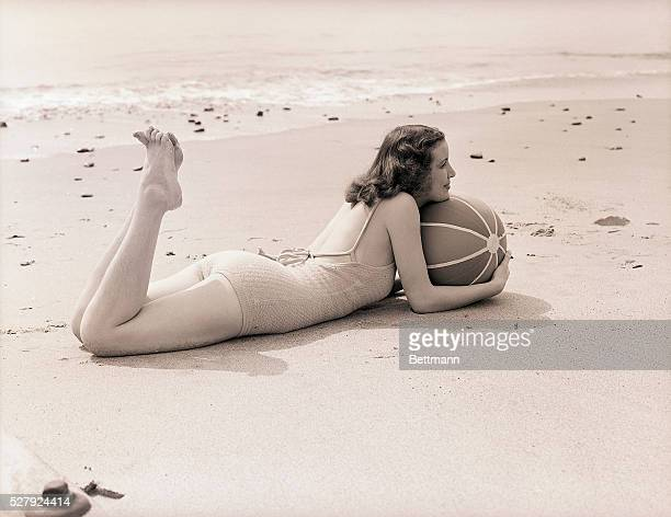 A young woman lies on the sand holding a beach ball She is shown fulllength in profile Undated photograph circa 1950's
