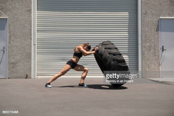 young woman lifting a giant tire - anstrengung stock-fotos und bilder