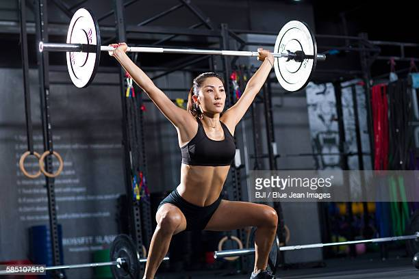 young woman lifting barbell at gym - asian female bodybuilder stock photos and pictures