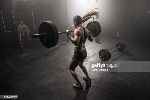 young woman lifting barbell, rear view - extra long stock pictures, royalty-free photos & images
