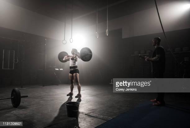 young woman lifting barbell, while trainer looks on - levantamento de peso imagens e fotografias de stock