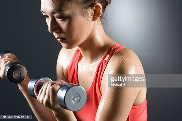Young woman lifting dumbbells, close-up, studio shot