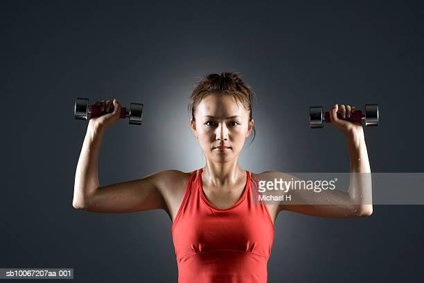 Young woman lifting dumbbells, portrait