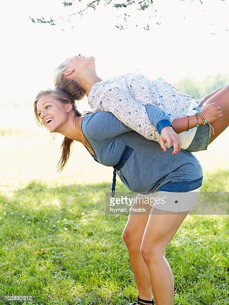 Young woman lifting friend on her back
