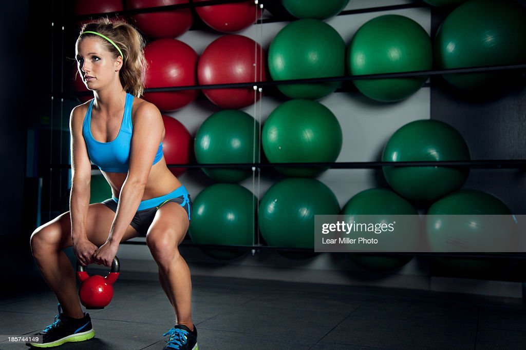 Young woman lifting kettlebell in gym : Foto de stock