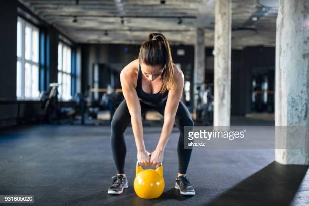 jeune femme kettlebell de levage dans la salle de gym - forte poitrine photos et images de collection