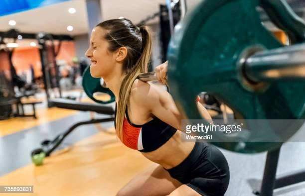 Young woman lifting weight in gym