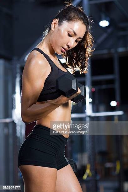 young woman lifting weights at gym - asian female bodybuilder stock photos and pictures