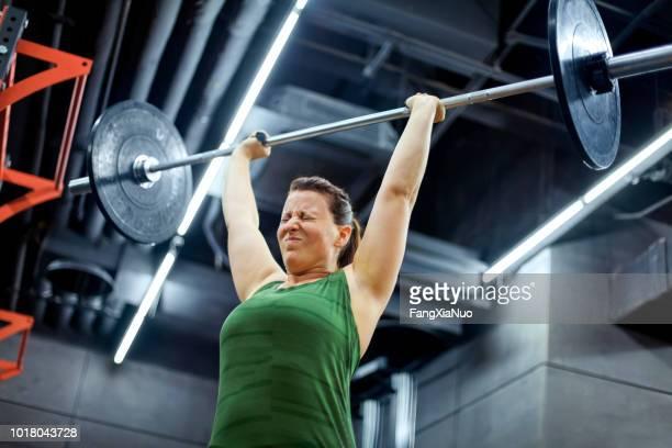 jonge vrouw gewichtheffen in de sportschool - hardnekkigheid stockfoto's en -beelden