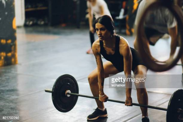 Young woman lifting weights on cross training