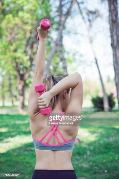 young woman lifting weights - bra top stock pictures, royalty-free photos & images
