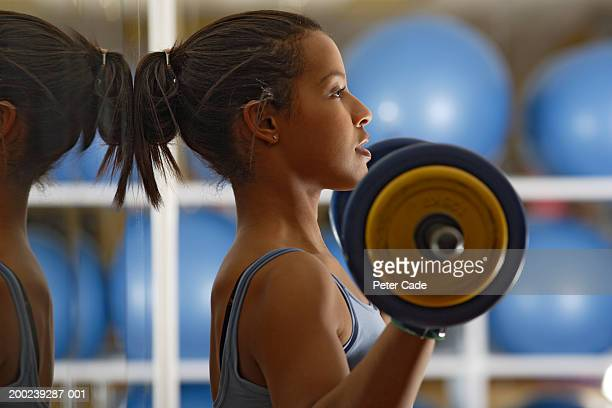 young woman lifting weights, side view - dumbbell stock pictures, royalty-free photos & images
