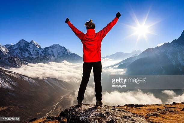 Giovane donna solleva le braccia a victory in Himalaya