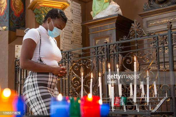 young woman lighting candles inside the church in times of coronavirus - in flames i the mask stock pictures, royalty-free photos & images