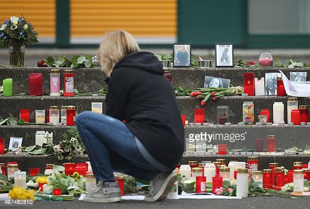 Young woman lights a cansle among candles, flowers and photographs of victims left by mourners at the Joseph-Koenig-Gymnasium high school to pay...