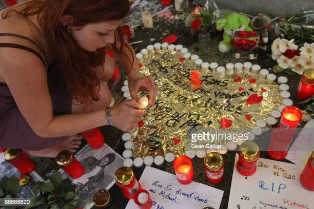 A young woman lights candles at a makeshift memorial to late US popstar Michael Jackson at the same time as Jackson's funeral services in California...