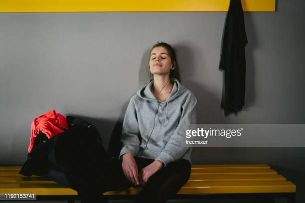 ロッカールームでのトレーニング後に音楽を聴く若い女性 - スポーツバッグ ストックフォトと画像