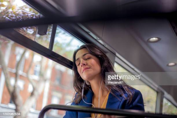 young woman listening music on a bus with earphones, eyes closed - differential focus stock pictures, royalty-free photos & images