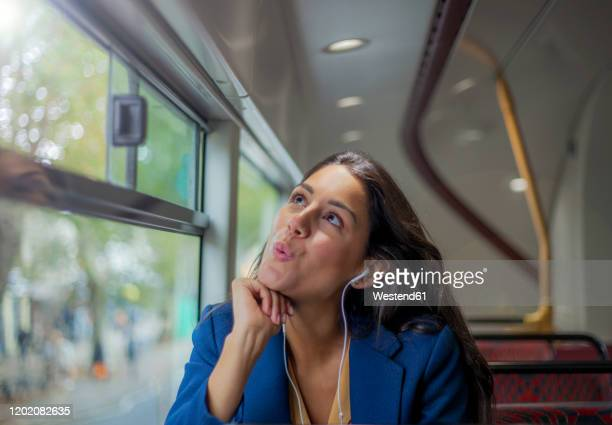young woman listening music on a bus with earphones - whistle stock pictures, royalty-free photos & images
