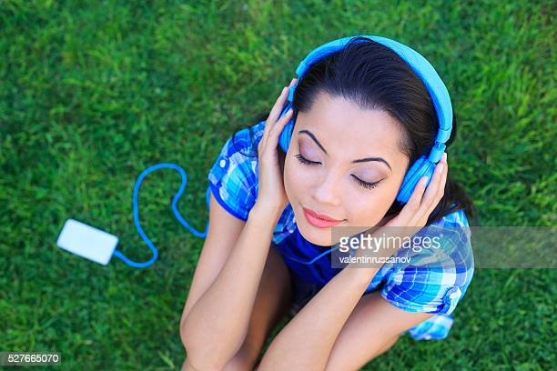 Young woman listening music on headphones