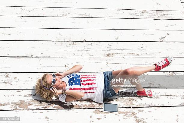 Young woman listening music on phone laying at floor