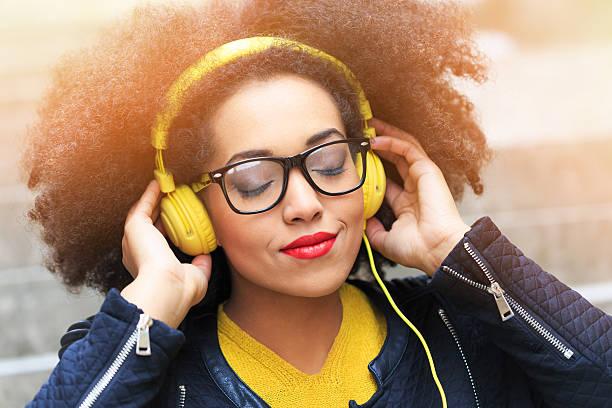 Jeune femme écoutant de la musique sur le casque jaune