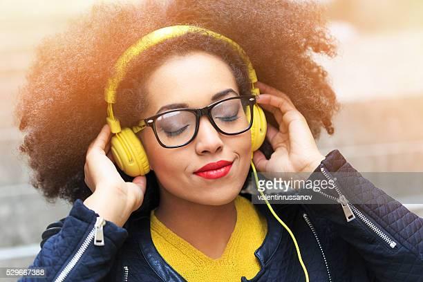 若い女性黄色のヘッドフォンで音楽を聞く