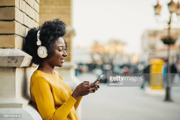 young woman listening music - podcasting stock pictures, royalty-free photos & images