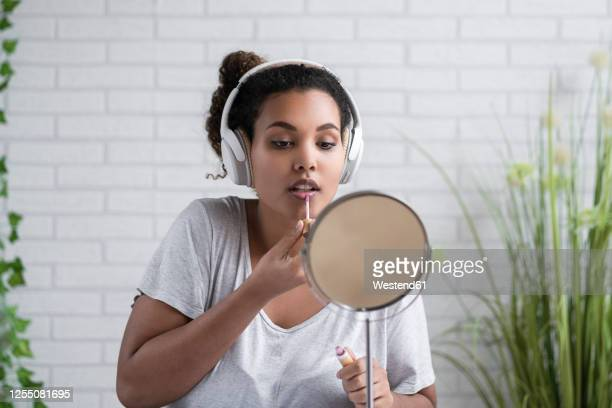 young woman listening music through headphones applying lip gloss at home - lip gloss stock pictures, royalty-free photos & images