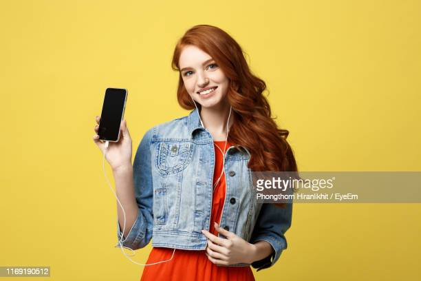 young woman listening music while standing against yellow background - mostrare foto e immagini stock