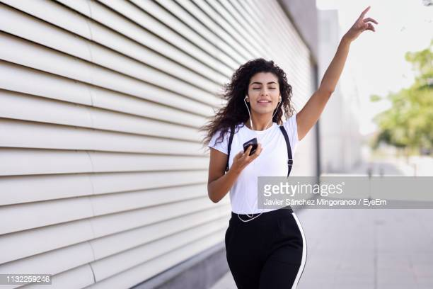 young woman listening music while walking on footpath by wall - muziek stockfoto's en -beelden