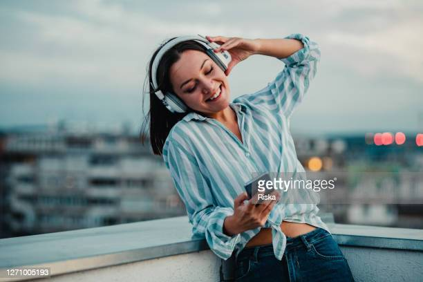 young woman listening music with headphones and enjoying in freedom - radio stock pictures, royalty-free photos & images
