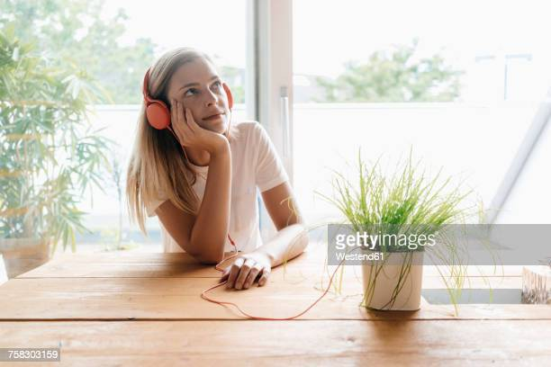 Young woman listening music with headphones plugged to potted plant