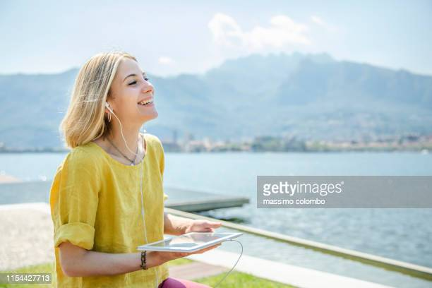 young woman listening podcast with digital tablet - radio broadcasting stock pictures, royalty-free photos & images