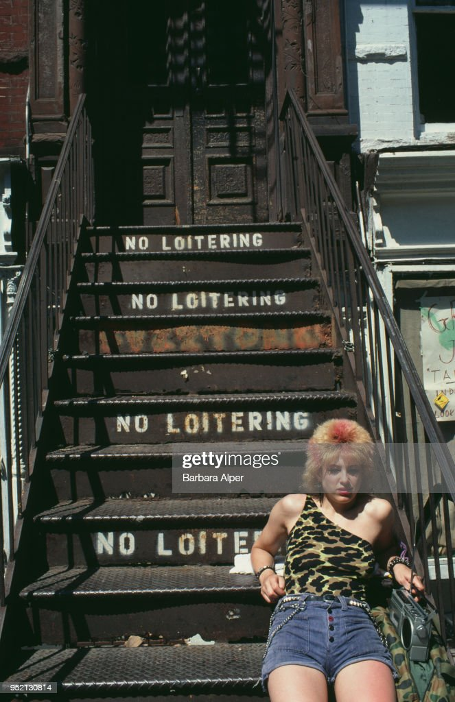 A young woman listening to a portable cassette-radio on a stairway painted with 'No Loitering' signs, East Village, New York City, July 1982.