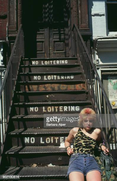 A young woman listening to a portable cassetteradio on a stairway painted with 'No Loitering' signs East Village New York City July 1982