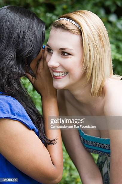 A young woman listening to another woman whisper
