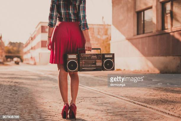Young woman listening to boom box outdoors and enjoying a beautiful day