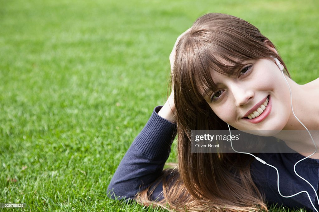 Young woman listening to earbuds : Stockfoto