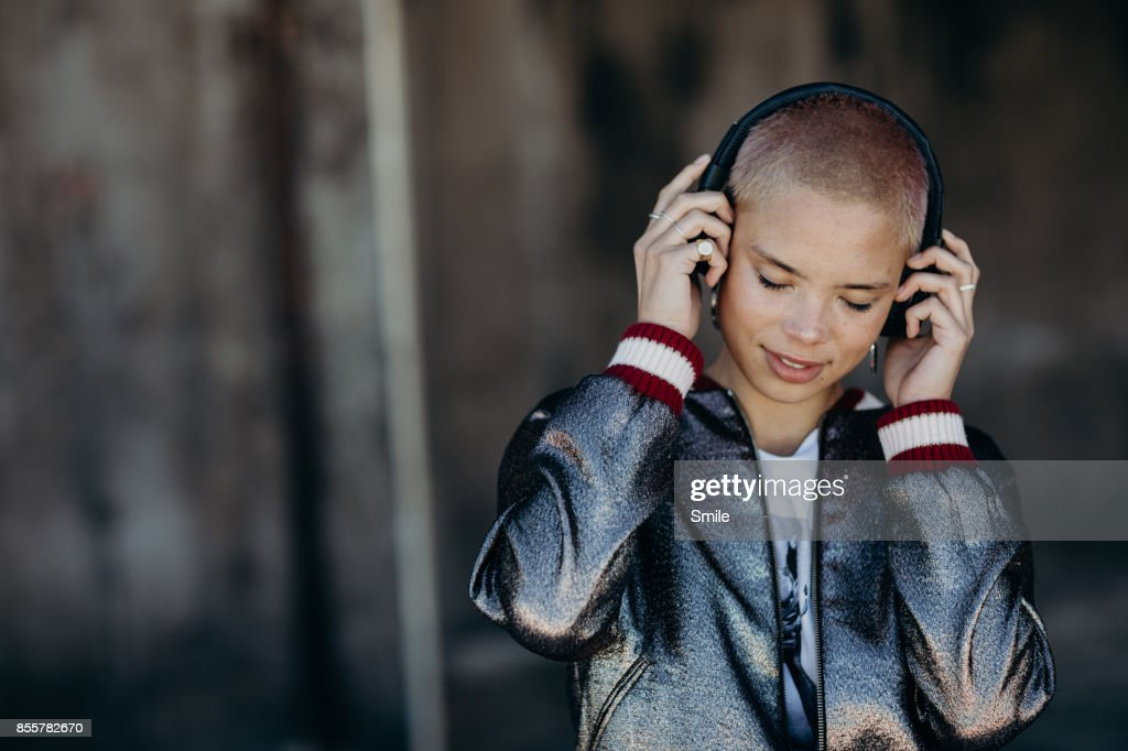 Young woman listening to headphone, smiling : Stock Photo