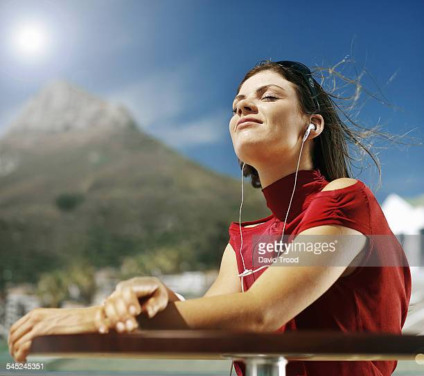 Young woman listening to headphones in the sun.
