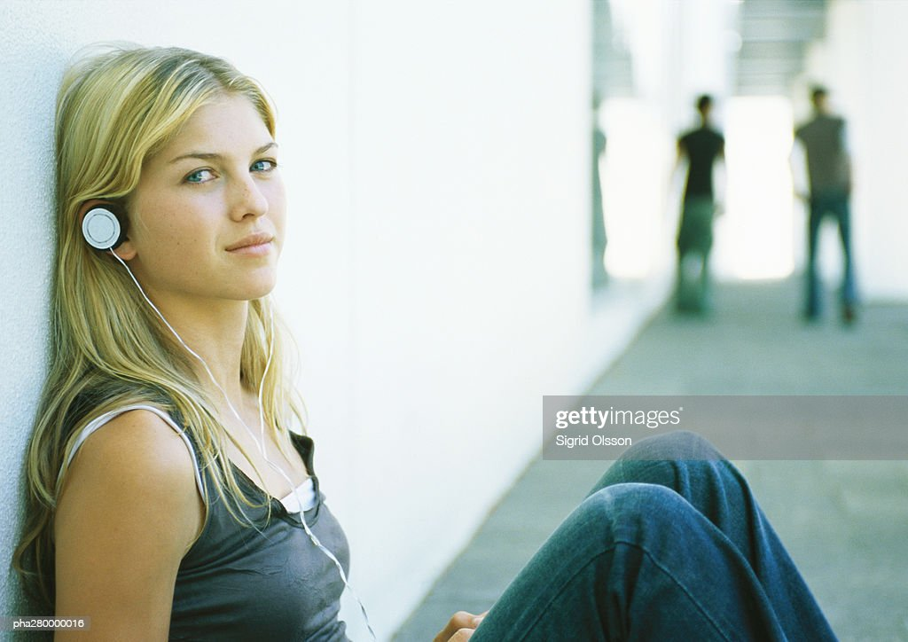 Young woman listening to headphones, looking at camera : Stockfoto