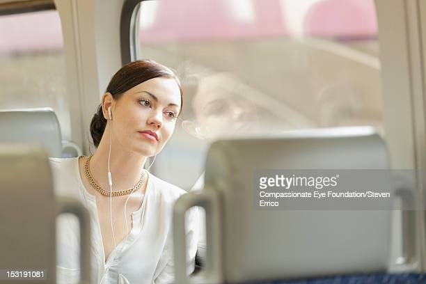 "young woman listening to headphones on train - ""compassionate eye"" fotografías e imágenes de stock"